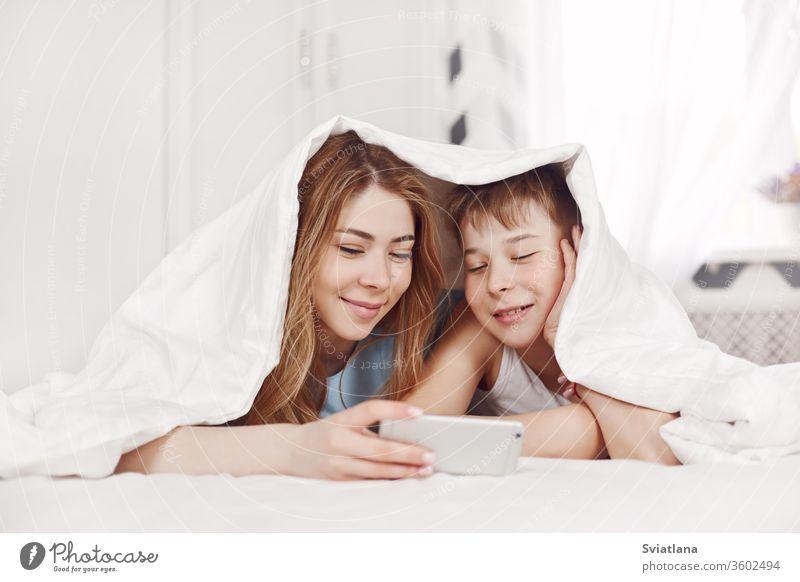 Ein hübsches junges Mädchen und ihr fröhlicher jüngerer Bruder sehen sich Fotos auf ihrem Telefon an, während sie lächelnd auf dem Bett liegen. Bruder und Schwester schauen sich Videos auf ihrem Telefon an.