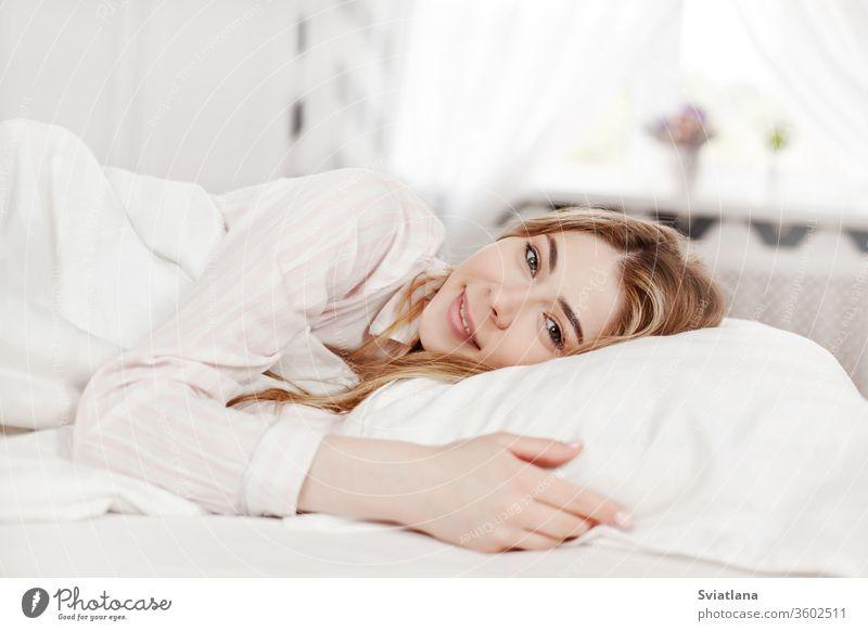 Ein junges attraktives Mädchen in gestreiften Pyjamas liegt morgens in ihrem Schlafzimmer im Bett. Seitenansicht Morgen Frau schön heimwärts schlafen Kopfkissen