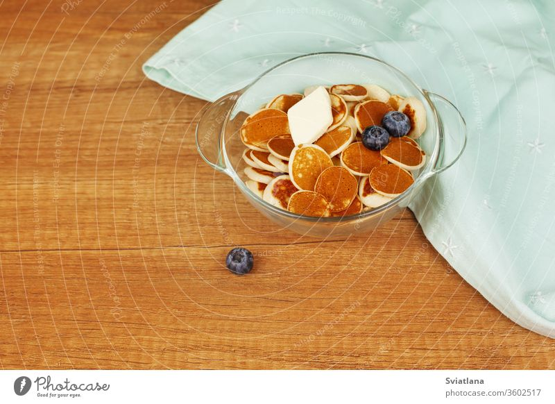 Mini-Pfannkuchen mit Butter und Heidelbeeren liegen in einem Teller auf einem Holztisch. Brunch, Dessert für Kinder, Trending Food. Platz für Text Müsli