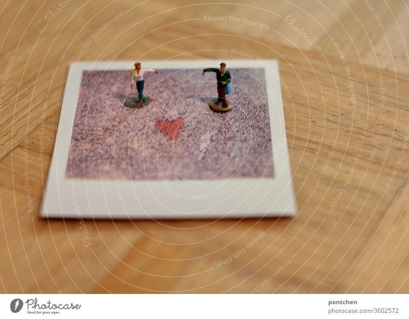 Zwei Figuren Mann und Frau stehen mit ausgebreitetem Arm auf einem Polaroid mit einem Herz. Liebe, symbolik. PoC. geschlechterrollen emanzipation einhaken tanz