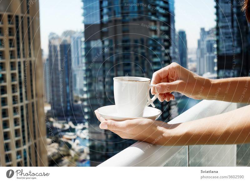 Ein Mädchen hält eine Tasse Kaffee vor dem Hintergrund moderner Gebäude. Eine Frau trinkt während der Selbstisolation auf dem Balkon einen Morgenkaffee
