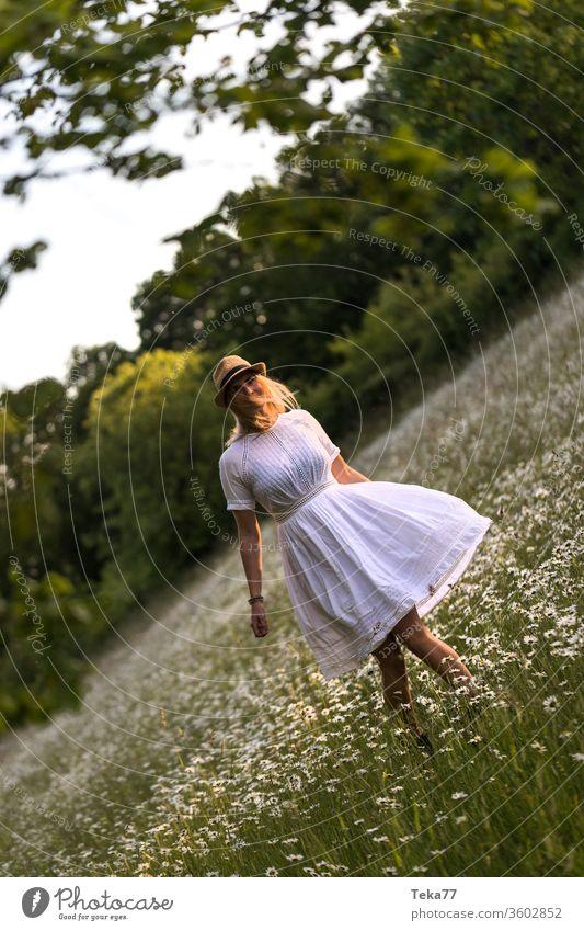 eine schöne blonde Frau in einem weißen Blumenfeld im Freien Natur Naturfotografie Junge Frau junge blonde Frau blondes Haar weißes Kleid Frau in der Natur