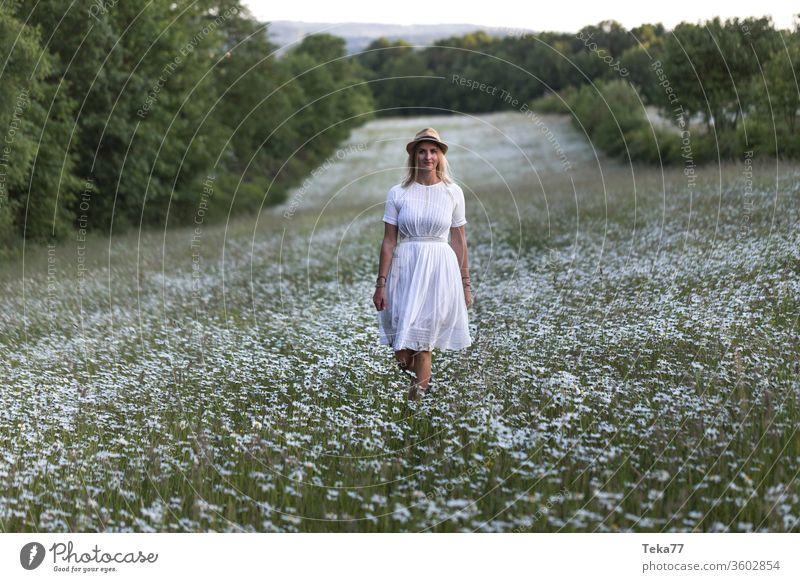 schöne blonde Frau in einem weißen Blumenfeld im Freien Natur Naturfotografie Junge Frau junge blonde Frau blondes Haar weißes Kleid Frau in der Natur magisch