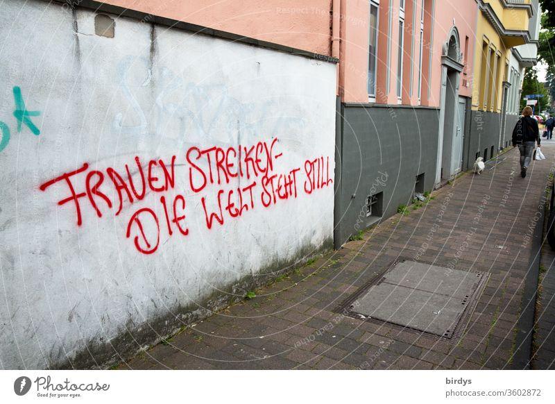 Wenn die Frauen streiken steht die Welt still. Frauenbewegung für Gleichstellung der Frau in Beruf und Bezahlung.Angemessene  Würdigung für die Leistung der Frau in der Gesellschaft. Grafitti auf einer Mauer
