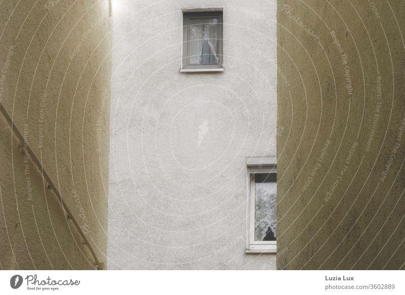 Blick durch eine enge Gasse auf die gegenüberliegende Hauswand mit zwei unscheinbaren Fenstern, dazu Spitzengardinen und etwas Sonnenschein in der oberen, linken Ecke