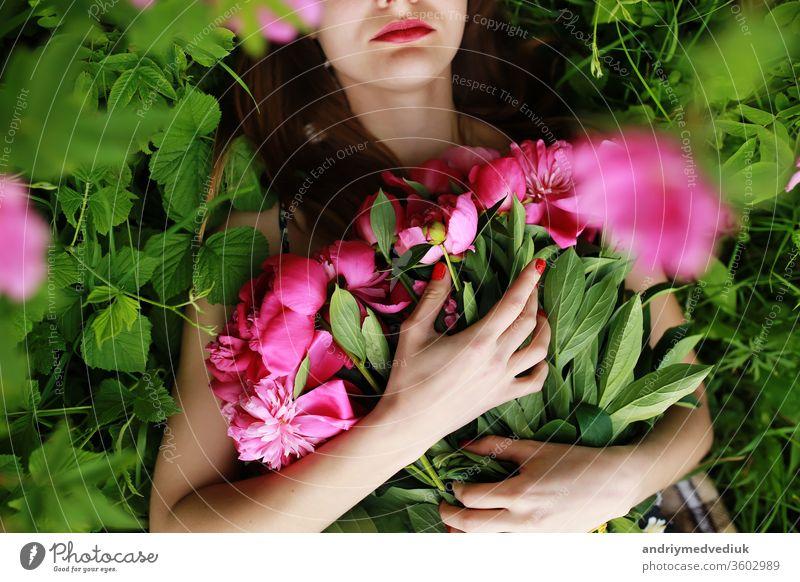 Strauß Pfingstrose. schöne junge Frau liegt unter Pfingstrosen. Feiertage und Veranstaltungen. Valentinstag. Frühlingsblüte. Blumen Porträt Glamour rosa