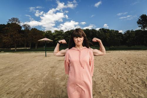 Das Mädchen zeigt ihre Muskeln. energisches junges Paar. Eine Frau in einem Sommerkleid zeigt ihren Bizeps. Starke Brünette. Schlankes Mädchen mit starken Händen. Der Mann hinter dem Mädchen zeigt einen Bizeps.