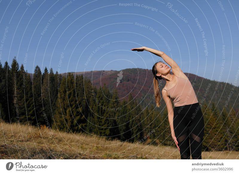 Junge Frau macht Dehnungsübungen in der Natur in den Bergen. Sportlerin beim Üben von Yoga-Pose in Leggins. schöne Waldlandschaft Zen sportlich Fitness