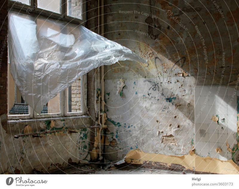 Durchzug - in einem alten maroden Gebäude mit zerstörtem Fenster weht ein Plastikvorhang vom Wind in die Höhe und lässt das Sonnenlicht herein Haus Wand Mauer