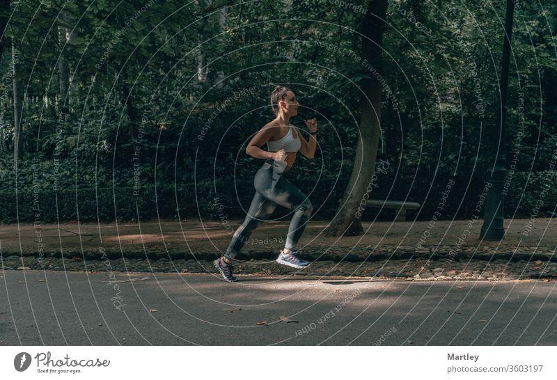 Selektiver Fokus in der Bewegung einer hübschen Sportlerin, die an einem Sommernachmittag eine von Bäumen umgebene Straße hinunterläuft. Fitte Frau beim körperlichen Training.