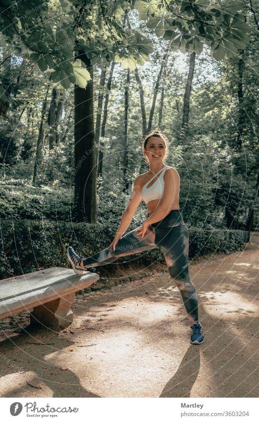 Junge hübsche Sportlerin mit Leggings, die lächelt und im Sommer in einem Wald mit frischer Luft Sport treibt. Frau Natur lächelnde Frau Kind jung im Freien