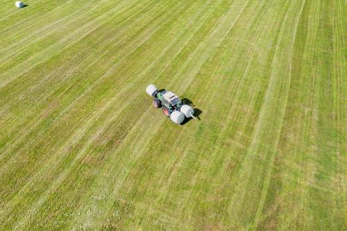 ein Traktor macht Heuballen auf einem Feld Traktor von oben historischer Traktor Heu machen grüner Traktor Traktor auf einem Feld landwirtschaftlich