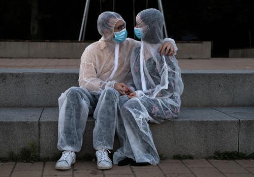 Pärchen kuschelt in Schutzanzügen und Masken Liebe Corona Schutzanzug Nähe Umarmung Sicherheit sicher absurd kuscheln Distanz Pandemie Coronavirus Corona-Virus