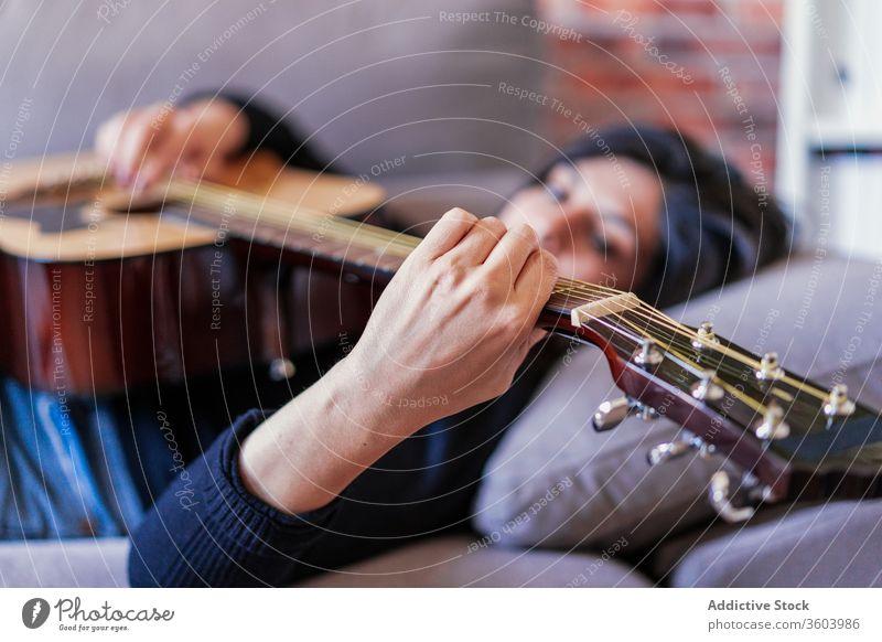 Frau spielt Gitarre und lernt mit Online-Kursen Musik Lifestyle im Innenbereich Lernen Spielen E-Learning Menschen Gitarrenspieler Erwachsener