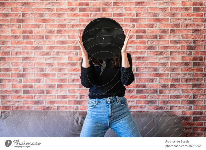 Anonyme junge Frau hält mit ihren Händen ein schwarzes Vinyl schön Mädchen Musik Disco Mode Klang Hintergrund Porträt Person Audio Menschen Entertainment