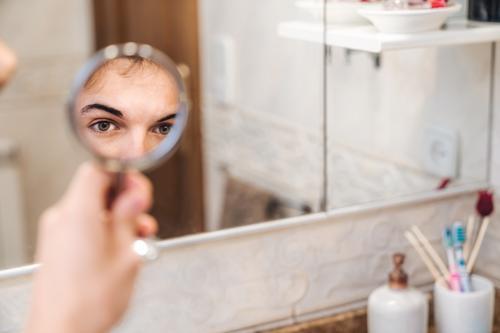 Hübscher Mann beim Blick in den Spiegel Bad Auge Morgen heimwärts hell ernst Routine täglich frisch männlich stehen Hygiene Stil Pflege Sauberkeit Zeitgenosse