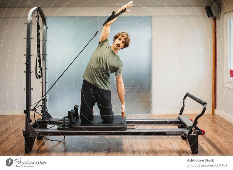 Sportlicher Mann benutzt Pilates-Reformer während des Trainings Dehnung sportlich Sportkleidung widersetzen Band Maschine Sportler Athlet Übung Fitness