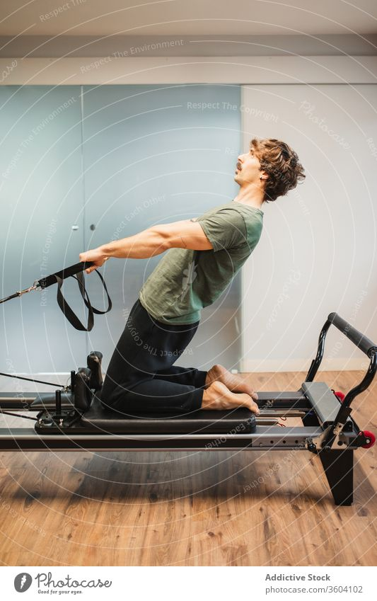 Sportlicher Mann benutzt Pilates-Reformer während des Trainings Dehnung sportlich Sportkleidung widersetzen Band Maschine männlich Sportler Athlet Übung Fitness