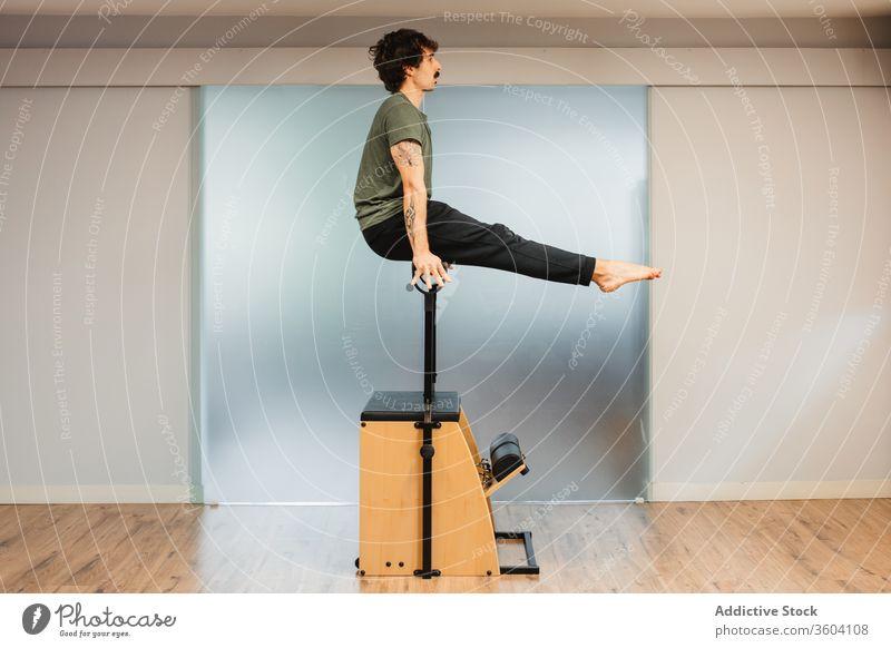 Athletischer Mann in Sportkleidung benutzt Pilates-Stuhl während des Trainings Sportler Fitnessstudio stark Gleichgewicht Übung männlich muskulös Kraft modern