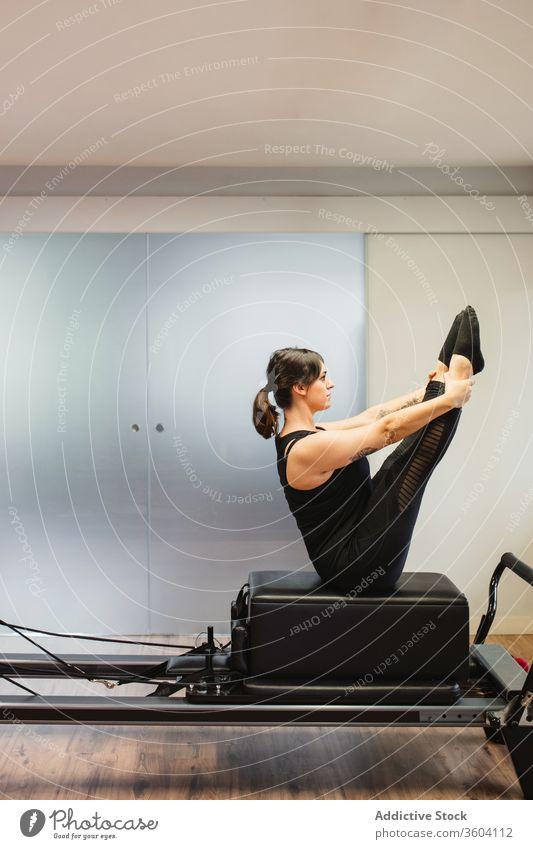 Sportlerin macht Übungen zum Pilates-Reformer Training Maschine Unterleib Sportkleidung Gesundheit Frau stark Athlet Wellness Sportbekleidung passen