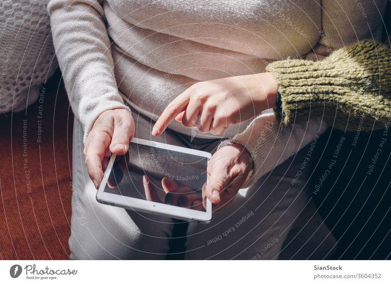 Erwachsene Frau und Tochter benutzen Tablette mit leerem Bildschirm. Senior online jung Hände Erwachsener Person Arzt Frauen verwenden digital zeigen weiß