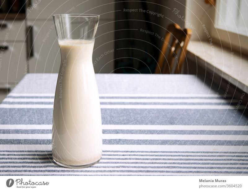 Frische hausgemachte Pflanzenmilch in einer Glaskaraffe, die auf dem Küchentisch steht. Gemütliche Atmosphäre des Interieurs, einfach, schlichte gesunde Hafermilch auf Tischdecke. Platz zum Kopieren.