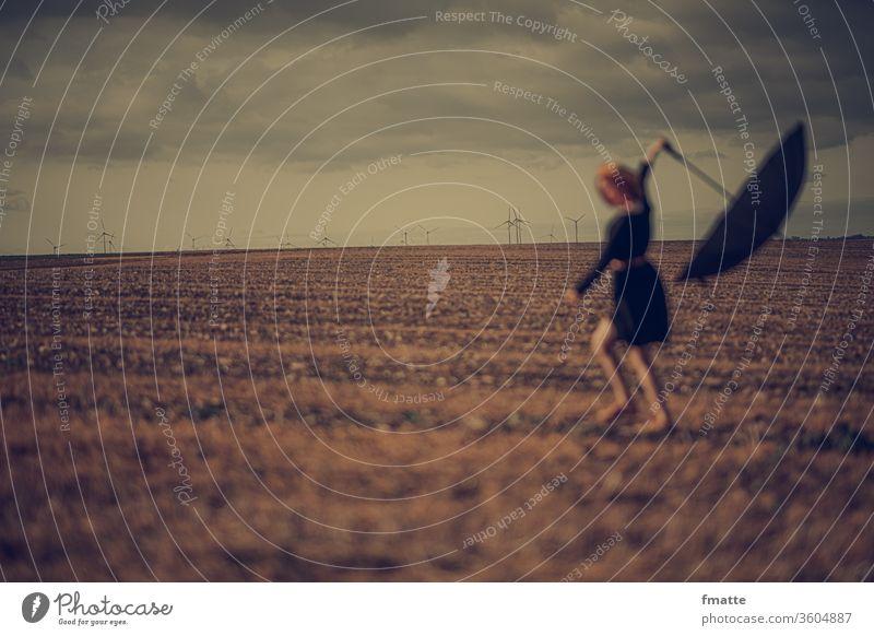 Frau mit Regeschirm auf einem Feld Regenschirm feld Windenergie Windkraftanlage Schirm Außenaufnahme Wetter Klima schlechtes Wetter Mensch Farbfoto Klimawandel