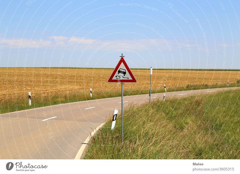 Glitschige Straße - Straßenschild steht an einer scharfen Kurve Zeichen rutschig Gefahr Verkehr gefährlich drehen. geschlängelt Ermahnung Pfeil Vorsicht