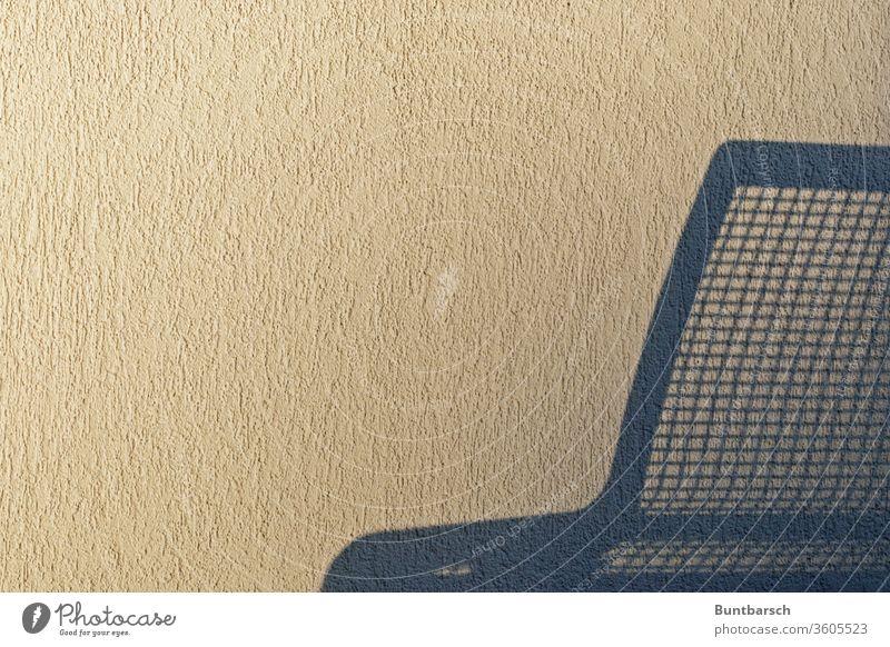 Schatten einer Sitzbank aus Metall an einer Rauhputzwand Bank Wand Menschenleer rauhputz Putz Mauer Farbfoto Textfreiraum unten Außenaufnahme weiß blau
