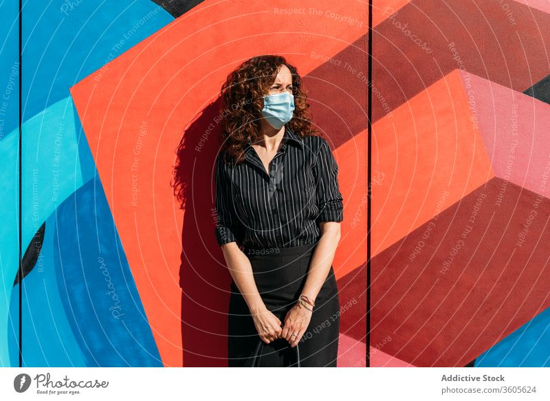 Frau mit Gesichtsmaske vor einer Wand mit leuchtenden Farben. Seuche Menschen Mundschutz Coronavirus Virus Schutz Grippe covid-19 krank Krankheit Gesundheit