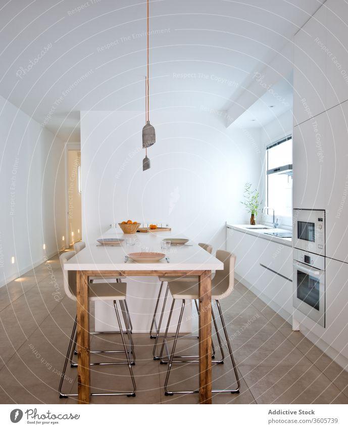 Interieur einer hellen Küche in einer modernen Wohnung Innenbereich Tisch Zeitgenosse sehr wenige skandinavisch Appartement einfach geräumig Stil Dekor Design