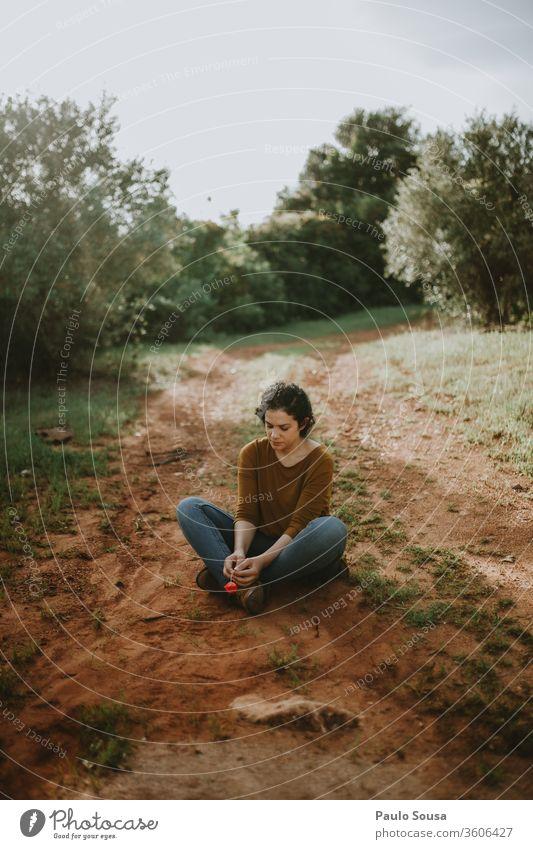 Frau sitzt auf unbefestigter Straße Sitzen auf dem Boden sitzend Warten warten Einsamkeit feminin Erholung Beine allein Liebeskummer reisen Denken