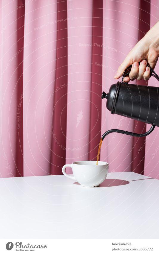 Frauenhand hält schwarze Metallkanne und gießt Kaffee oder Tee in weiße Tasse vor rosa Draperie, selektiver Fokus Getränk Morgen trinken Becher Frühstück