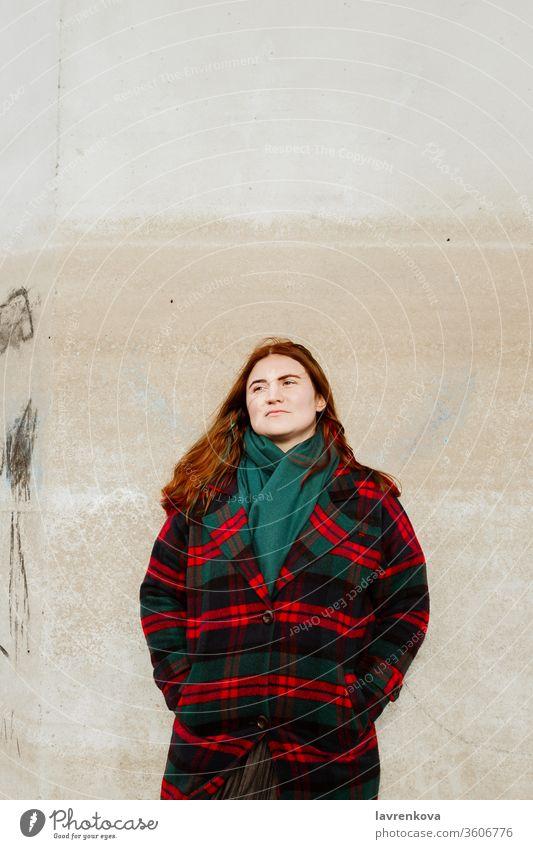 Hündin mit roten Haaren in kariertem Mantel im Freien stehend Frau rote Haare Herbst Plaid allein Lifestyle Erwachsener geprüft Wand Wegsehen Saison Winter