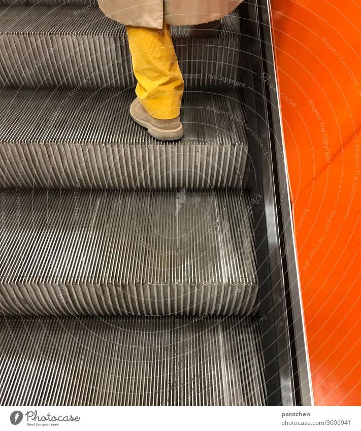 Knallig gelbes Hosenbein trifft knallig orange Seitenwand einer Rolltreppe. Mode und Stil. Unterwegs sein Knallfarben rolltreppe kleidung mode farbkontrast