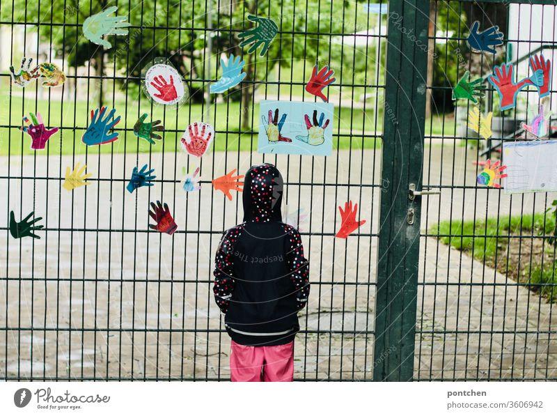 Ein Kind in Regenkleidung steht traurig vor  einem geschlossenen Kindergarten.Rückansicht.  Ausgangsbeschränkungen, Corona, Schließungen sehnsucht kindergarten