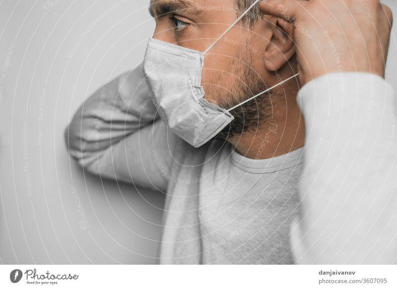 Ein Mann setzt sich eine medizinische Maske auf das Gesicht Coronavirus Quarantäne covid-19 Gesundheit Mitteilung Schutz Corona-Virus Schutzmaske