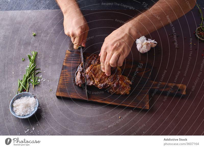 Hände beim Schneiden von Rindersteak ribeye Steak gegrillt schwarz angus Grillrost Lebensmittel Fleisch Küche Beefsteak gebraten geschmackvoll aufgeschnitten