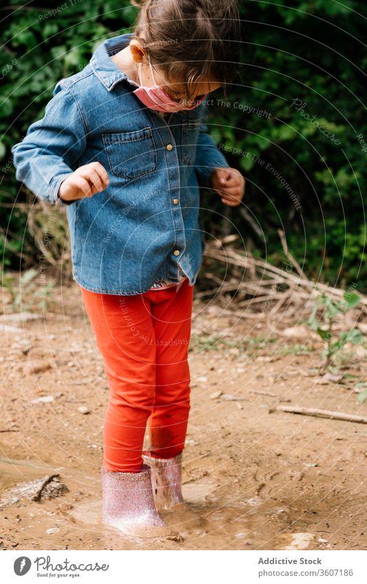 Neugieriges Mädchen mit chirurgischer Maske spielt in Schlammpfütze Kind Pfütze Spaß haben neugierig Gummi Stiefel niedlich dreckig Wasser nass bezaubernd