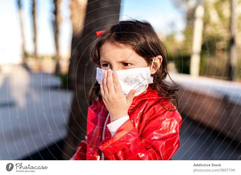Ethnisches Mädchen mit chirurgischer Maske auf der Straße medizinisch Mundschutz Kind genießen Wochenende Bund 19 behüten ethnisch Kindheit heiter Großstadt