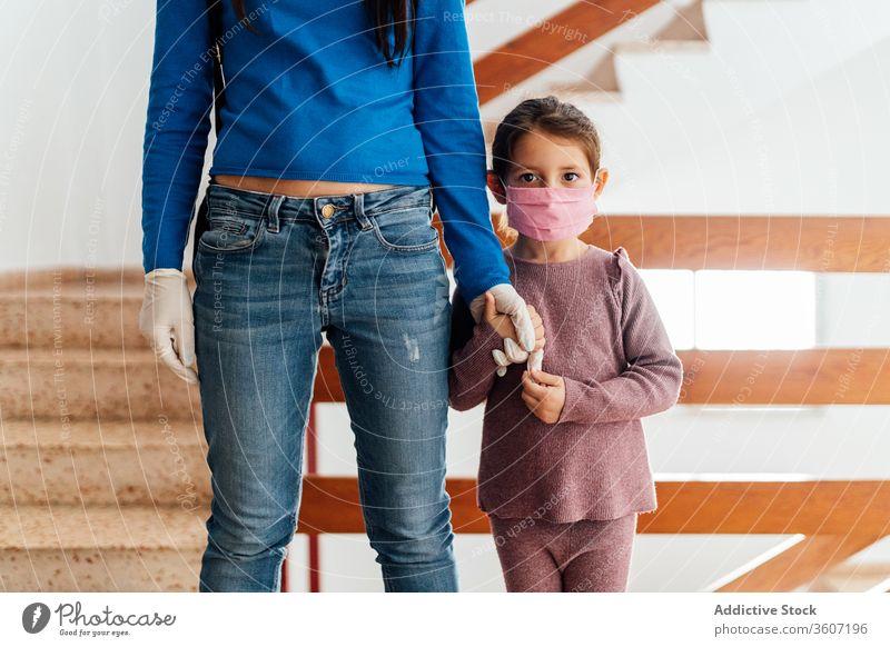 Mädchen mit medizinischer Maske hält Hand der Mutter behüten Mundschutz Coronavirus Tochter Kind Ausbruch Sicherheit Gesundheitswesen ethnisch chirurgisch