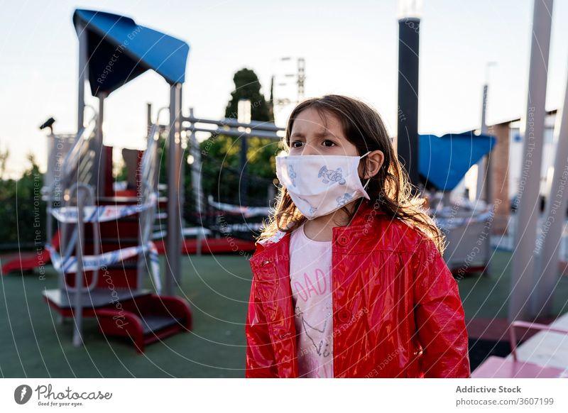 Stirnrunzelndes Mädchen mit medizinischer Maske auf dem Spielplatz Kind Mundschutz beunruhigt Ausbruch Coronavirus Großstadt ethnisch Kindheit modern urban