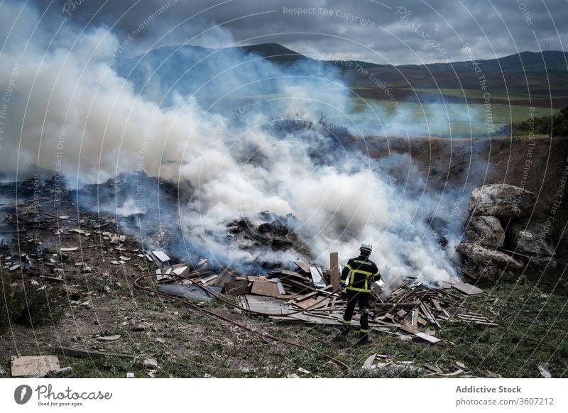 Feuerwehrmann löscht Feuer mit Wasser Mut Schlauch löschen Rauch ausmachen Uniform männlich behüten Arbeit Gerät Job stehen Beruf Schutzhelm Sicherheit Arbeiter