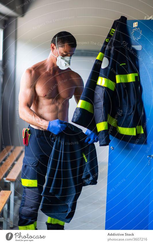 Leitender männlicher Feuerwehrmann auf der Feuerwache Feuerwehrhaus Arbeit Mann Atemschutzgerät Sicherheit Senior stark Spind nackter Torso ernst vorbereiten