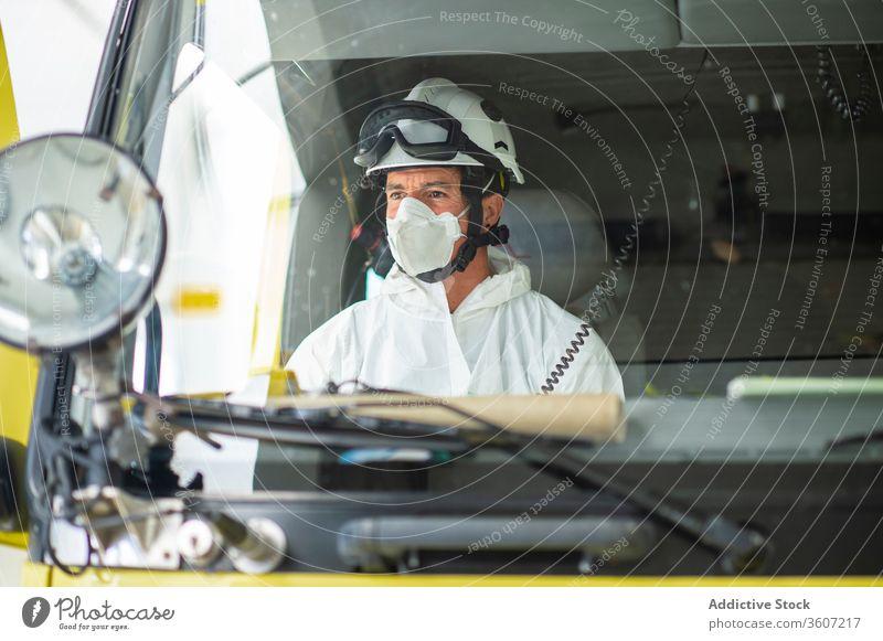 Schwerer Feuerwehrmann in Schutzuniform in einem Auto Mann behüten Uniform Atemschutzgerät männlich Schutzhelm Feuerwehrhaus Tracht medizinisch Mundschutz