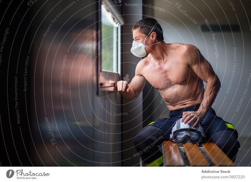 Muskulöser Feuerwehrmann mit Atemschutzgerät in der Feuerwache Feuerwehrhaus Mann Sicherheit behüten Arbeit reif Schutzhelm männlich stark nackter Torso ernst