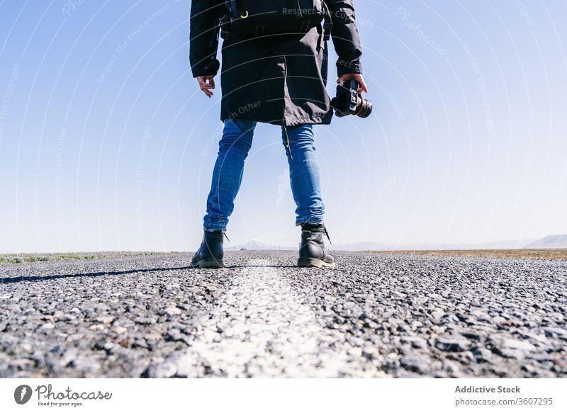 Männlicher Fotograf auf der Straße Mann professionell Reisender Landschaft malerisch Asphalt Fotoapparat kalt männlich Island Fotografie Fahrbahn Abenteuer