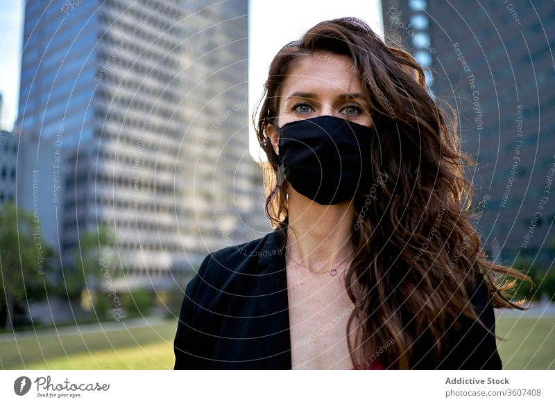 Seriöse Frau mit medizinischer Maske in der Stadt Seuche Coronavirus Mundschutz Großstadt Bund 19 behüten verhindern Sicherheit Stadtzentrum ernst modern