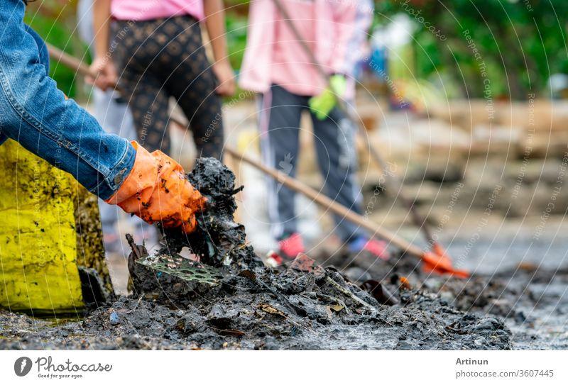 Freiwillige Erwachsene und Kinder, die am Meeresstrand Müll sammeln. Umweltverschmutzung am Strand. Aufräumen von Müll am Strand. Die Menschen tragen orange Handschuhe und sammeln den Müll in einem gelben Sack ein.