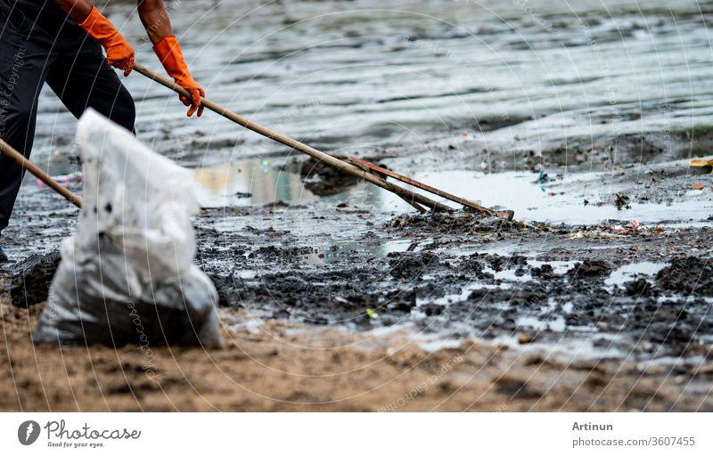 Freiwillige Helfer benutzen den Rechen, um den Müll aus dem Meer zu fegen. ฺBeach Reiniger, der den Müll am Meeresstrand in einer durchsichtigen Plastiktüte sammelt. Freiwillige, die den Strand säubern. Aufräumen von Müll am Strand.